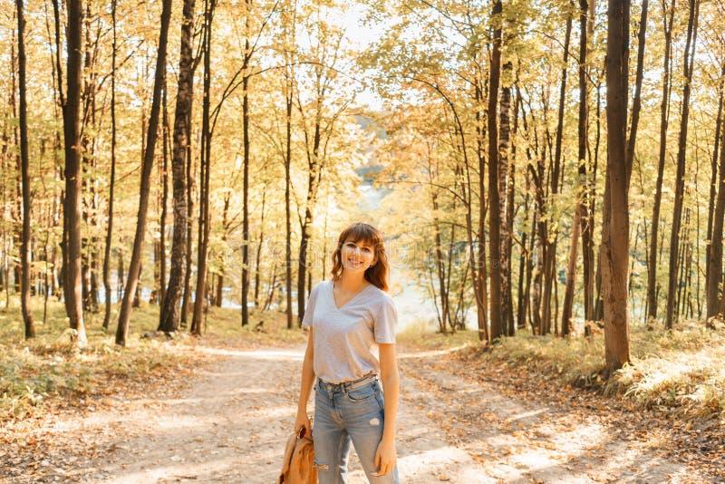 Retrato de la mujer joven en parque del otoño Árboles con el follaje amarillo en el fondo, luz hermosa de la puesta del sol calie fotografía de archivo