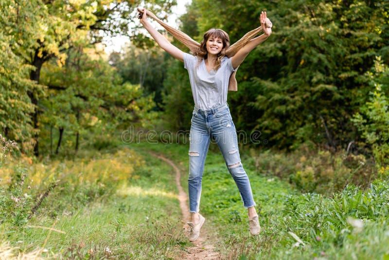 Retrato de la mujer joven en parque del otoño Árboles con el follaje amarillo y verde en el fondo, luz hermosa de la puesta del s fotografía de archivo