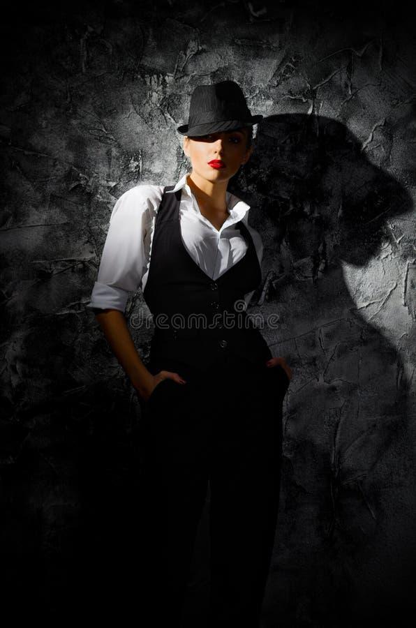 Retrato de la mujer joven en sombrero en la pared imagenes de archivo