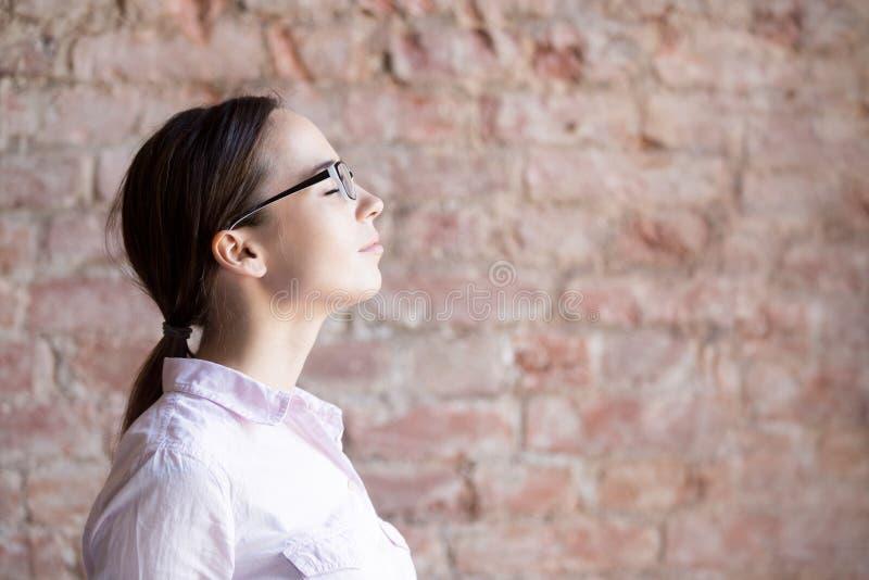Retrato de la mujer joven en la sonrisa de las lentes foto de archivo