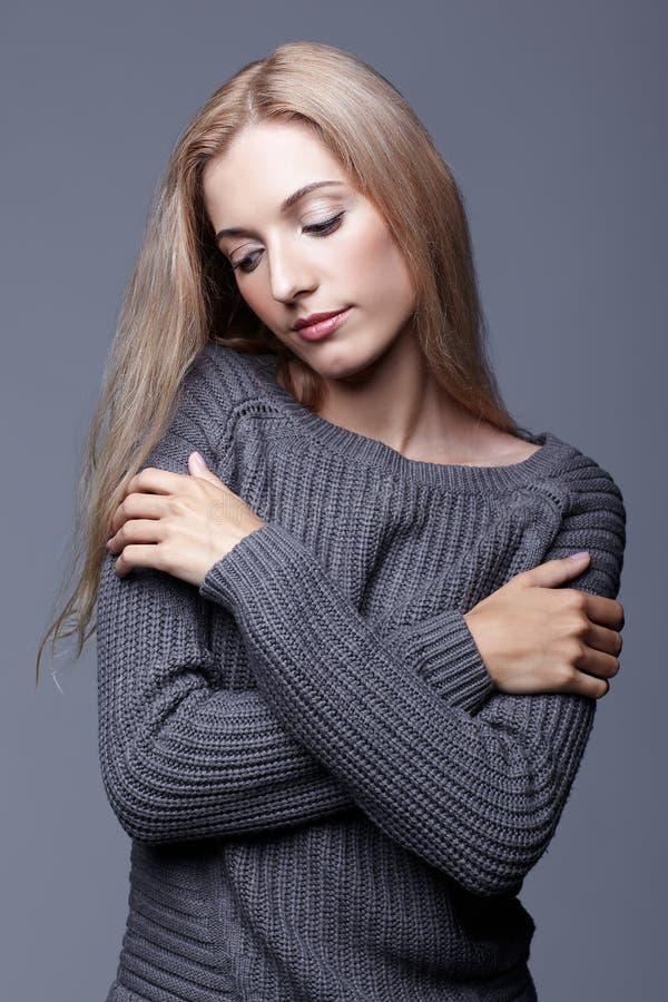 Retrato de la mujer joven en suéter de lana gris con el crosse de las manos imagen de archivo