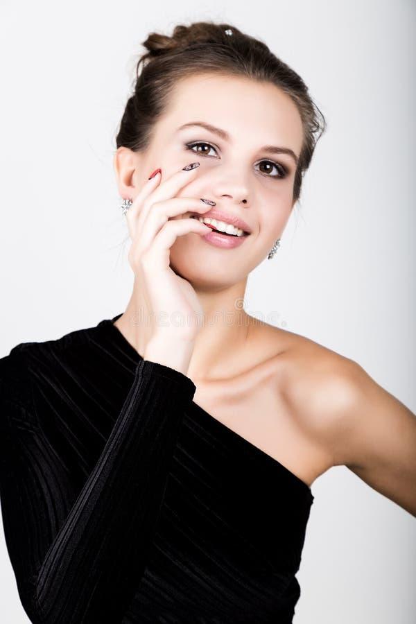 Retrato de la mujer joven en un vestido negro, llevando a cabo las manos cerca de la cara, ella sorprendió fotos de archivo