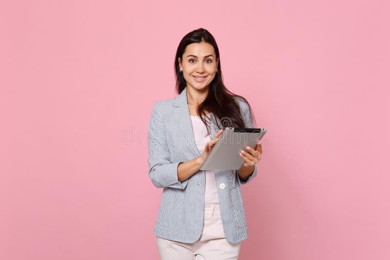 Retrato de la mujer joven encantadora sonriente en chaqueta rayada usando el ordenador de la PC de la tableta aislado en la pared foto de archivo