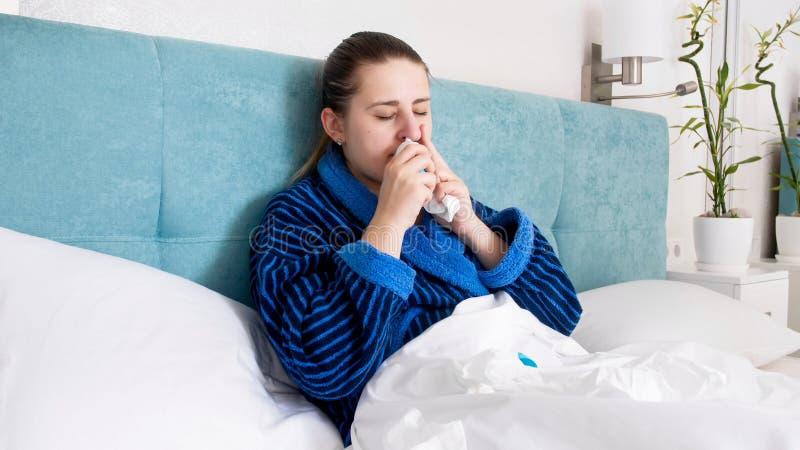 Retrato de la mujer joven enferma con la gripe que miente en cama y que usa el espray nasal fotos de archivo libres de regalías