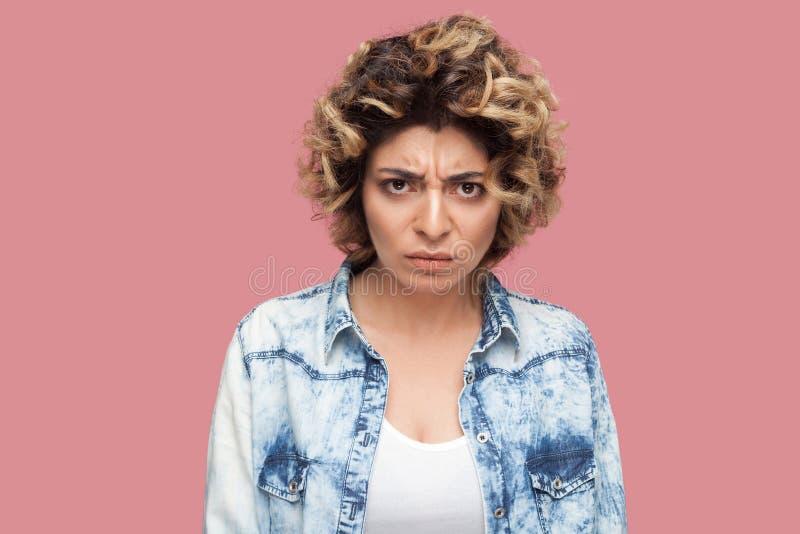 Retrato de la mujer joven enojada con el peinado rizado en la situación azul casual de la camisa y de mirar la cámara con la cara imágenes de archivo libres de regalías