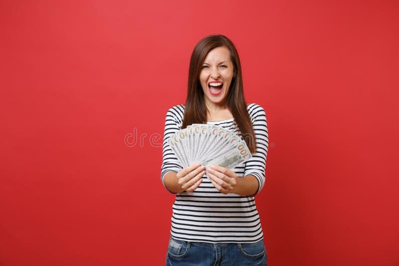 Retrato de la mujer joven extática en ropa rayada que grita sosteniendo porciones del paquete de dinero del efectivo de los dólar imagen de archivo