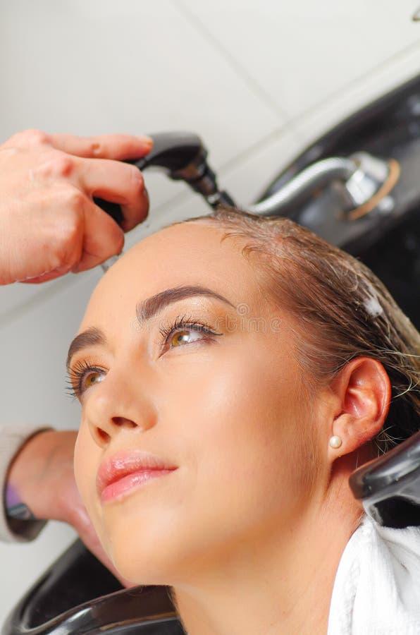 Retrato de la mujer joven feliz con la cabeza que se lava del peluquero en el salón de pelo foto de archivo libre de regalías