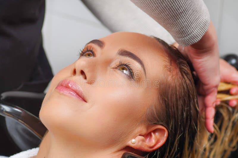 Retrato de la mujer joven feliz con la cabeza que se lava del peluquero en el salón de pelo, la belleza y el concepto de la gente foto de archivo