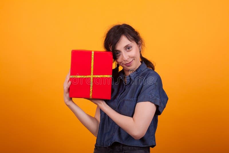 Retrato de la mujer joven feliz con su caja de regalo roja que mira la cámara en estudio sobre fondo amarillo fotografía de archivo