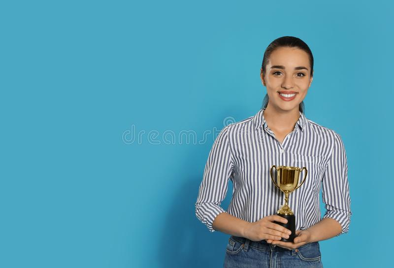 Retrato de la mujer joven feliz con la taza del trofeo del oro en el fondo azul, espacio para imagen de archivo libre de regalías