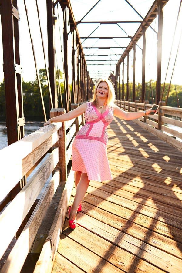 Retrato de la mujer joven feliz que camina en el puente fotografía de archivo