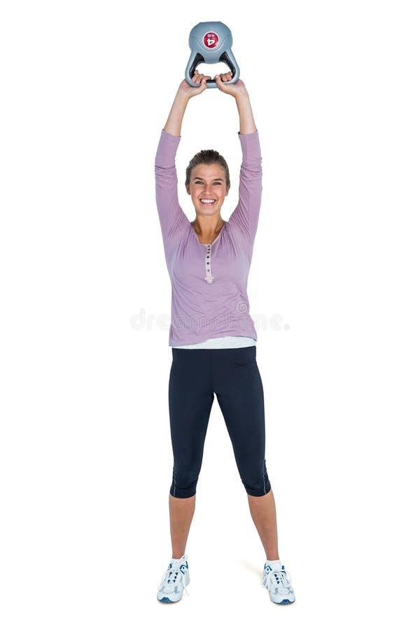 Retrato de la mujer joven feliz que ejercita con el kettlebell foto de archivo