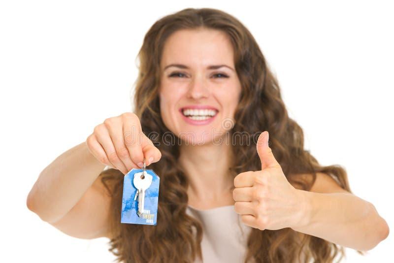 Retrato de la mujer joven feliz que muestra llave de la casa imagen de archivo