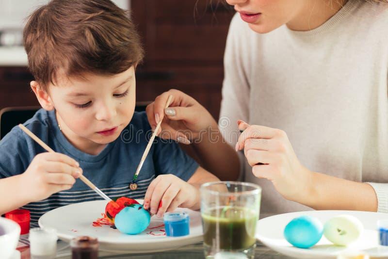 Retrato de la mujer joven feliz que pinta los huevos de Pascua con su pequeño hijo adorable fotos de archivo libres de regalías