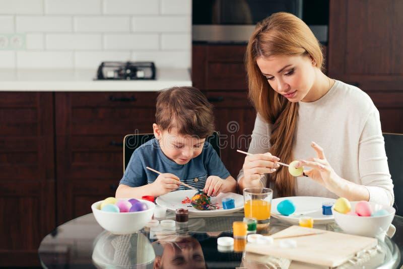Retrato de la mujer joven feliz que pinta los huevos de Pascua con su pequeño hijo adorable foto de archivo libre de regalías