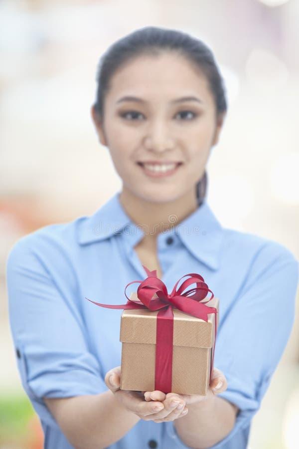 Retrato de la mujer joven feliz que presenta una caja de regalo fotos de archivo libres de regalías