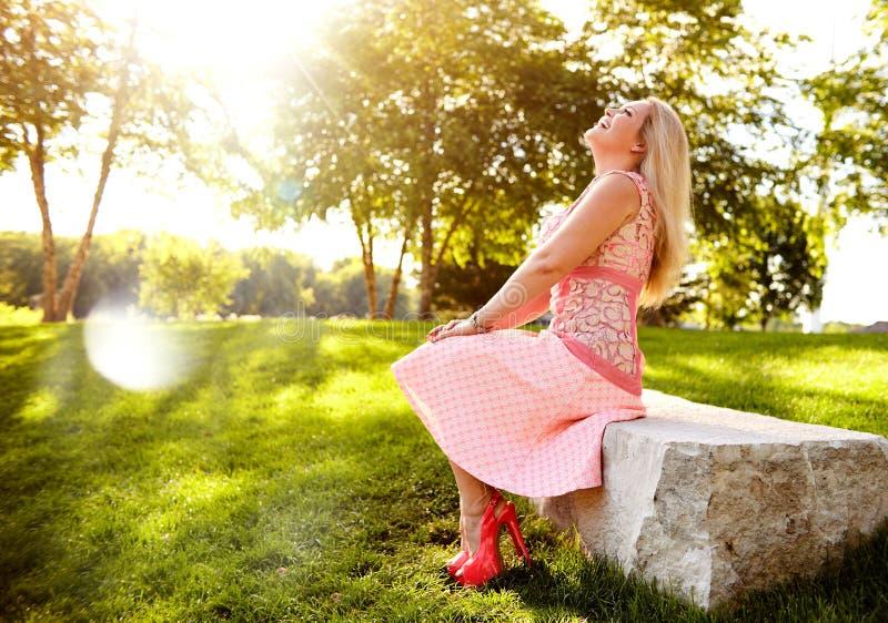 Retrato de la mujer joven feliz que se sienta en piedra foto de archivo libre de regalías