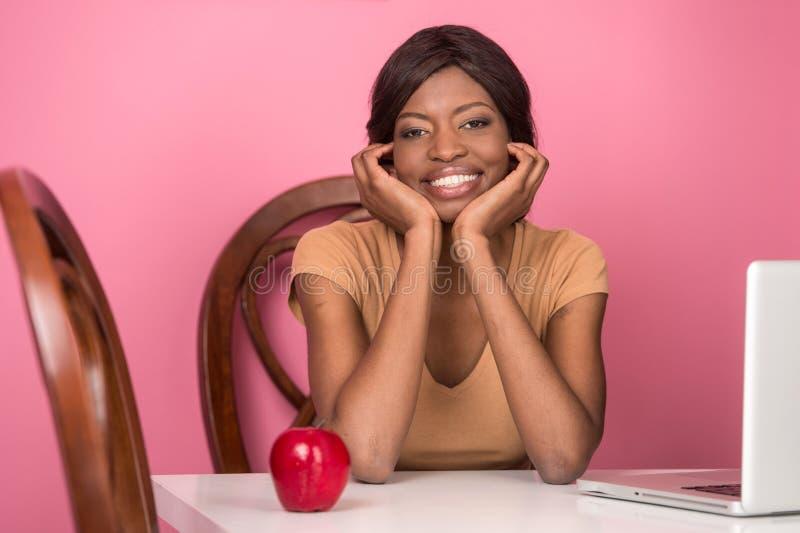 Retrato de la mujer joven feliz que usa el ordenador portátil fotos de archivo libres de regalías