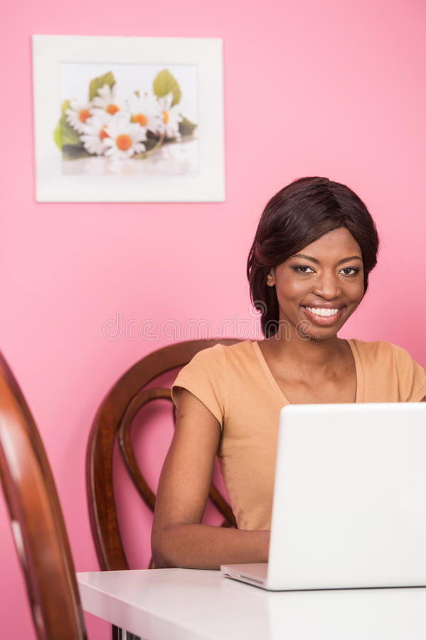 Retrato de la mujer joven feliz que usa el ordenador portátil imagen de archivo libre de regalías