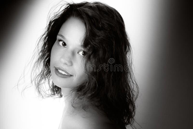 Retrato de la mujer joven feliz sobre el fondo blanco en la imagen blanca negra del vintage retro del tiro del estudio del fotógr fotografía de archivo