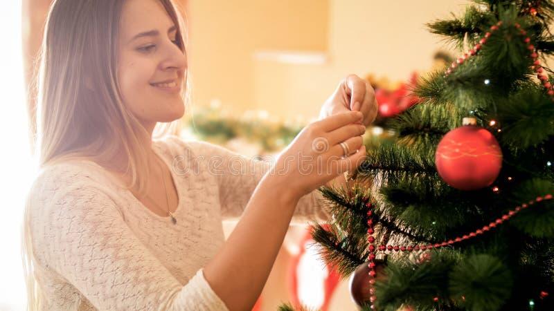 Retrato de la mujer joven feliz sonriente que adorna el árbol de navidad en la mañana imagenes de archivo