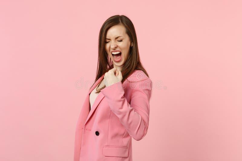 Retrato de la mujer joven de griterío extática con el puño de apretón cerrado de los ojos como ganador en rosa en colores pastel imagenes de archivo