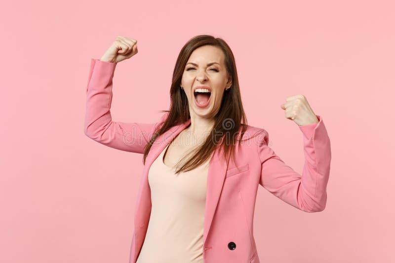 Retrato de la mujer joven de griterío extática en puños de apretón de la chaqueta como el ganador aislado en la pared rosada en c foto de archivo