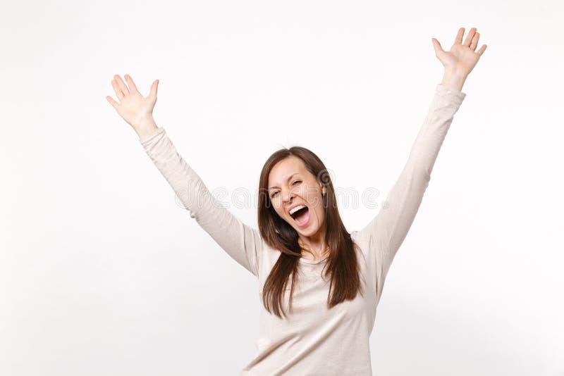 Retrato de la mujer joven de griterío extática feliz en la ropa ligera que sube, manos de extensión aisladas en la pared blanca fotografía de archivo libre de regalías