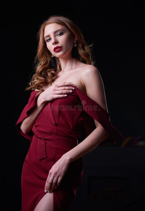 Retrato de la mujer joven hermosa atractiva en vestido rojo bajado imagenes de archivo