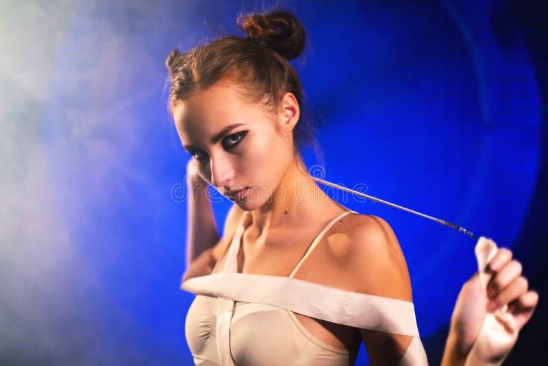Retrato de la mujer joven hermosa bochornosa del gimnasta que presenta con la cinta de la gimnasia imagen de archivo