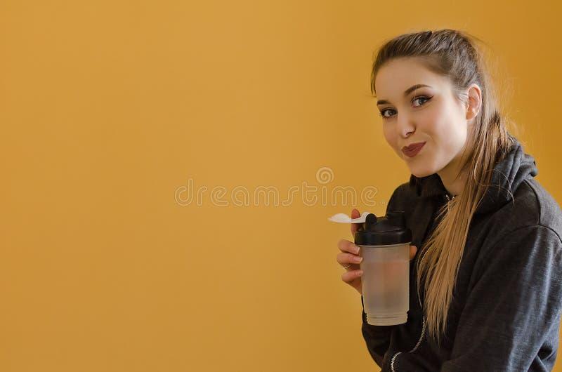 Retrato de la mujer joven hermosa con agua de botella del deporte imagenes de archivo