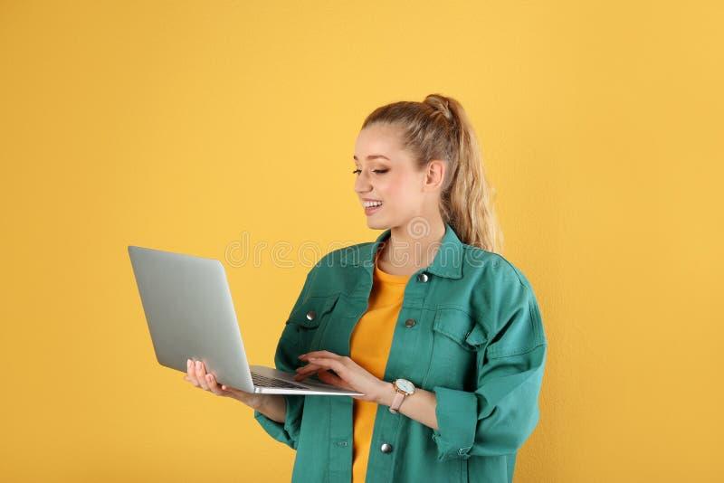 Retrato de la mujer joven hermosa con el ordenador portátil en amarillo imagenes de archivo