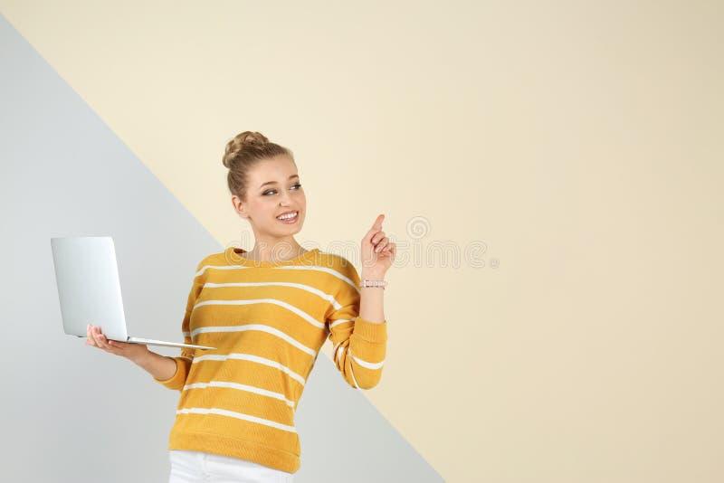 Retrato de la mujer joven hermosa con el ordenador portátil en fondo del color fotografía de archivo libre de regalías