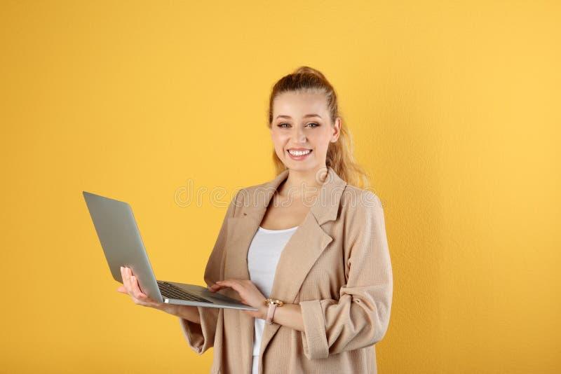 Retrato de la mujer joven hermosa con el ordenador port?til fotografía de archivo libre de regalías
