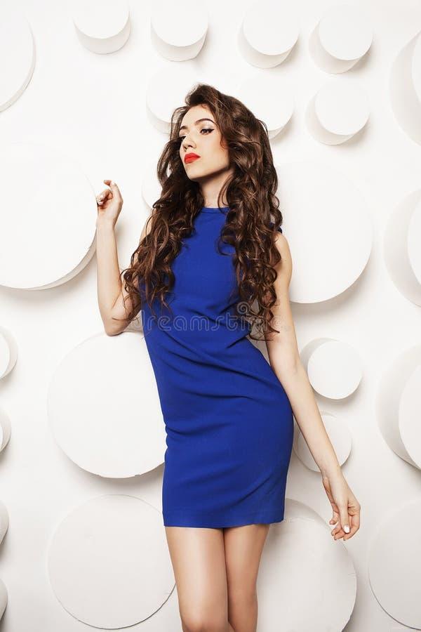 Retrato de la mujer joven hermosa con el pelo marrón largo rizado en vestido azul imagen de archivo