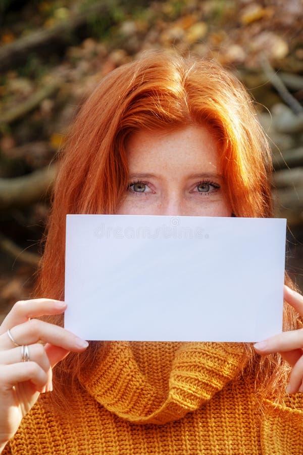 Retrato de la mujer joven hermosa con el pelo rojo, jengibre, en suéter anaranjado sonriendo sosteniendo un papel en blanco en bl imagen de archivo