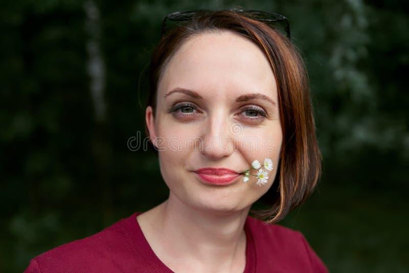 Retrato de la mujer joven hermosa con la flor blanca en la boca, ascendente cercano de la cara imagenes de archivo