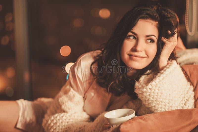 Retrato de la mujer joven hermosa con la taza de bebida caliente en interior casero acogedor foto de archivo libre de regalías