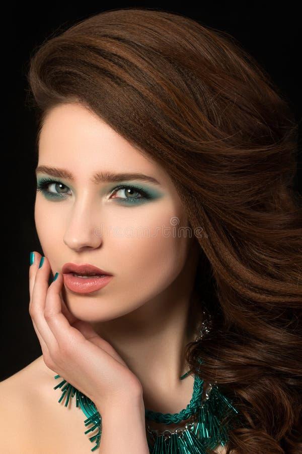 Retrato de la mujer joven hermosa con los clavos azules y el maquillaje del ojo fotografía de archivo libre de regalías