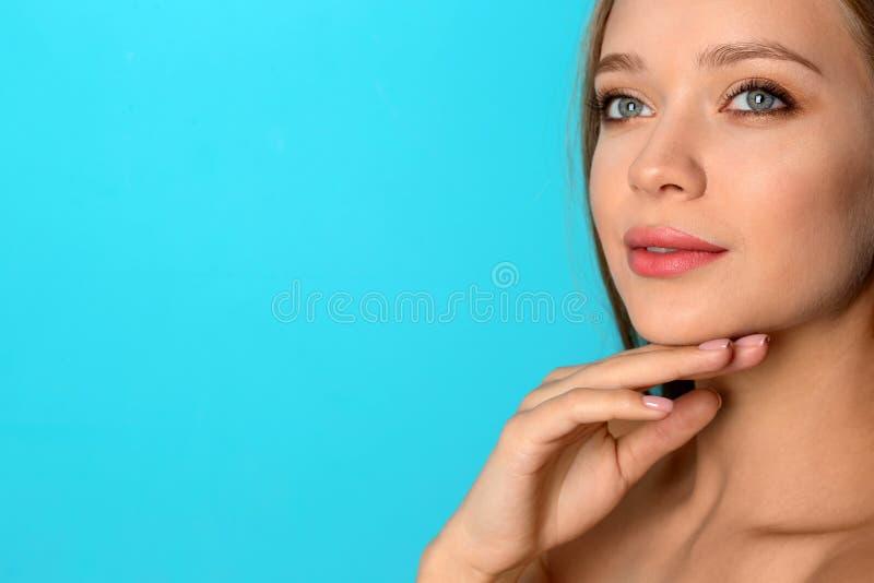 Retrato de la mujer joven hermosa con maquillaje natural en fondo del color foto de archivo libre de regalías