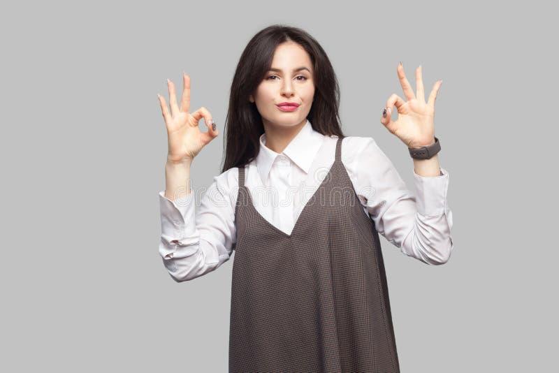 Retrato de la mujer joven hermosa en la camisa blanca y del delantal marrón con maquillaje y la situación morena del pelo y la mi imagenes de archivo