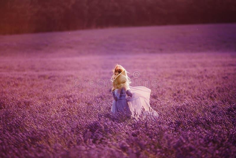 Retrato de la mujer joven hermosa en campo púrpura de la lavanda fotografía de archivo