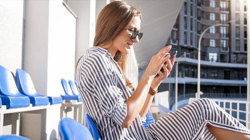 Retrato de la mujer joven hermosa en gafas de sol usando el teléfono móvil en la calle imagen de archivo