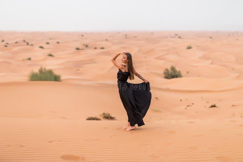 Retrato de la mujer joven hermosa en la presentaci?n negra larga del vestido que agita al aire libre en el desierto arenoso imágenes de archivo libres de regalías