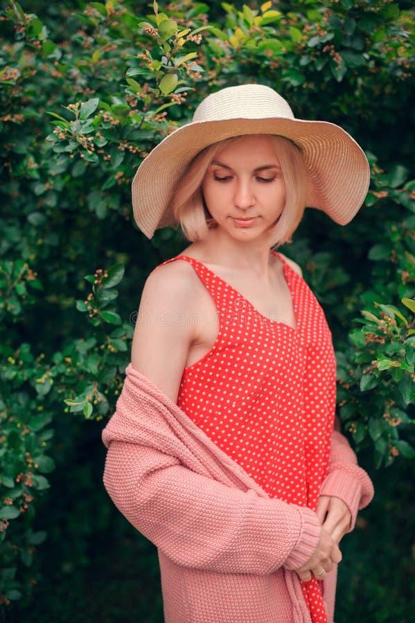 Retrato de la mujer joven hermosa en sombrero ancho de la playa, contra el fondo del parque del verde del verano fotos de archivo