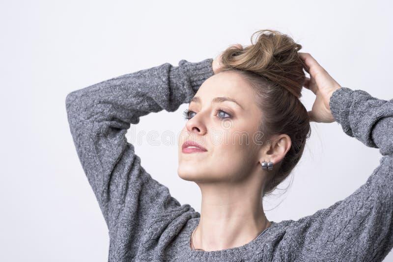Retrato de la mujer joven hermosa independiente que hace el peinado del bollo del pelo mismo fotografía de archivo