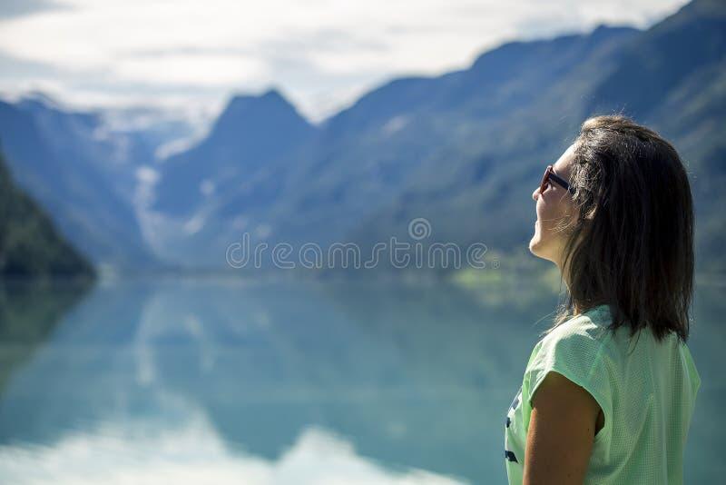 Retrato de la mujer joven, hermosa que defiende cerca el lago de la montaña en Noruega fotos de archivo