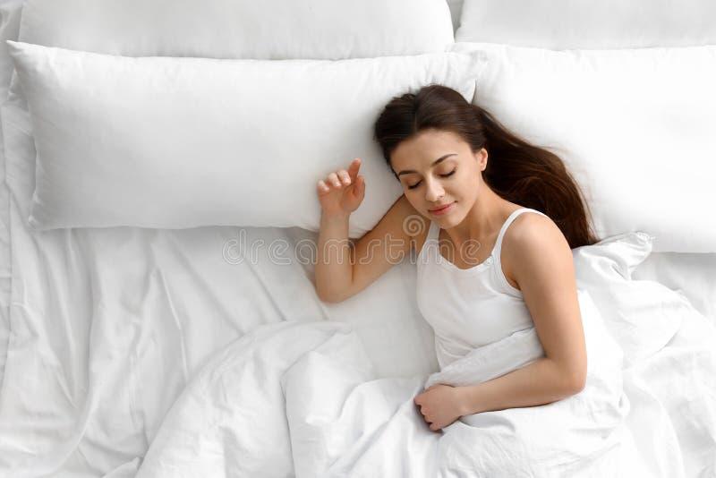 Retrato de la mujer joven hermosa que duerme en cama grande, arriba imágenes de archivo libres de regalías