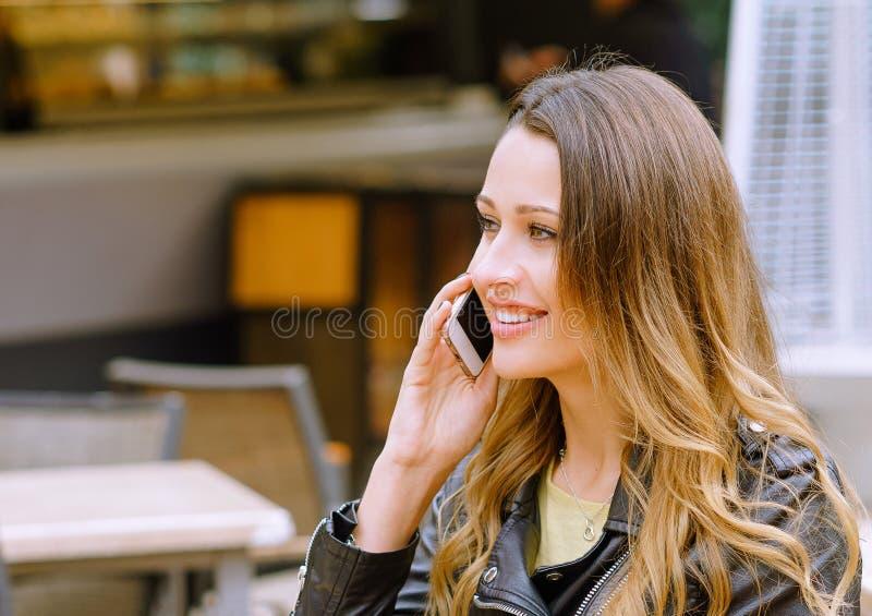 Retrato de la mujer joven hermosa que habla en smartphone al aire libre foto de archivo