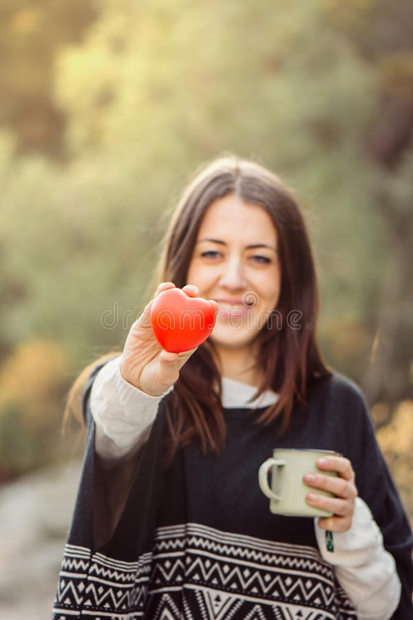 Retrato de la mujer joven hermosa que lleva a cabo el corazón rojo imagen de archivo libre de regalías